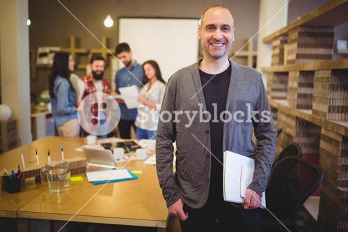 Confident businessman standing by table in creative office
