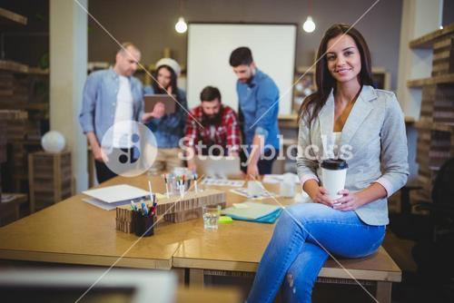 Businesswoman holding disposable cup while sitting on table