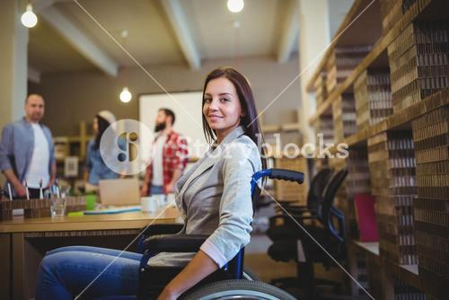 Businesswoman on wheelchair by desk