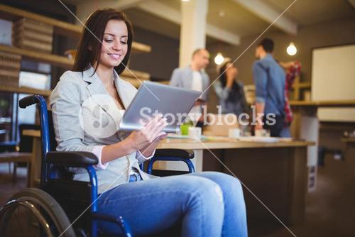 Disabled young businesswoman using digital tablet