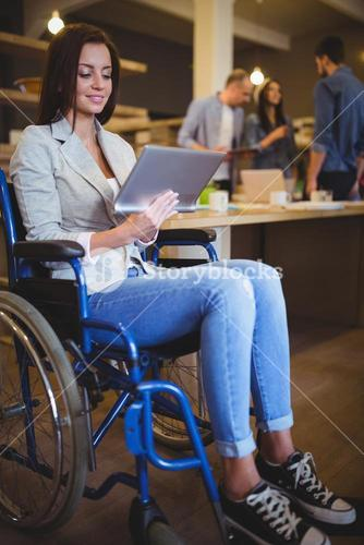 Disabled businesswoman smiling while using digital tablet