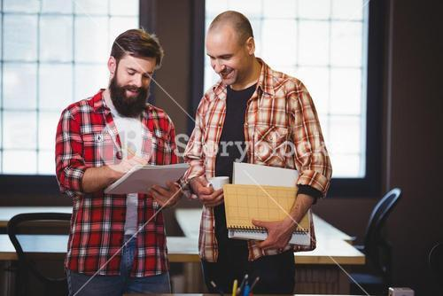 Hipster discussing over notebook with male coworker