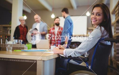 Confident disabled businesswoman writing at desk