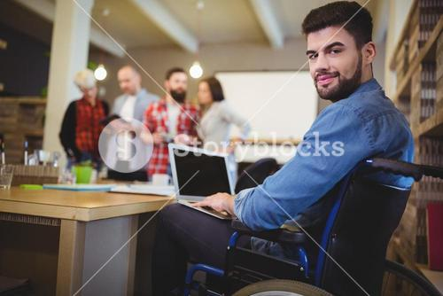 Smart disabled businessman using laptop at desk