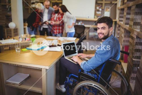 Confident disabled businessman using laptop at desk