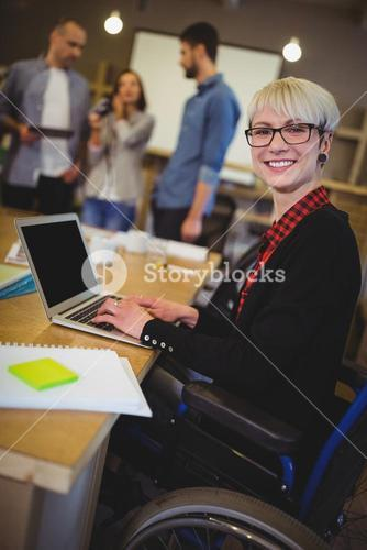 Smiling disabled businesswoman using laptop at desk