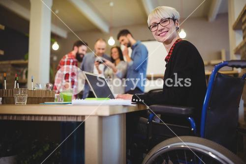 Happy disabled businesswoman using laptop at desk