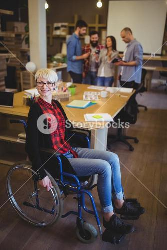 Portrait of young disabled businesswoman by desk
