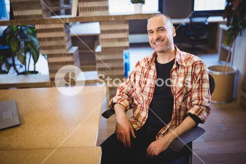 Businessman sitting by desk in creative office