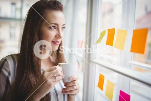 Businesswoman looking through window while having coffee in creative office