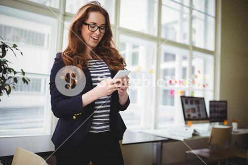 Businesswoman using phone at creative office