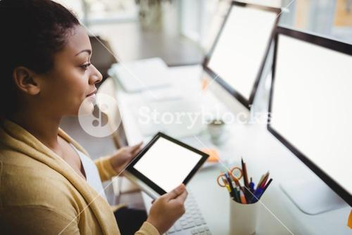 Businesswoman looking at computer while using digital tablet in creative office