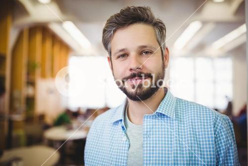 Portrait of businessman smiling in office cafeteria