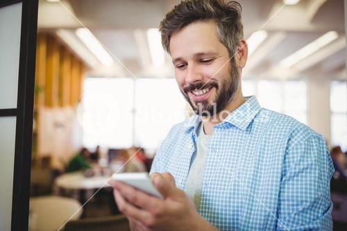 Happy businessman using phone in cafeteria