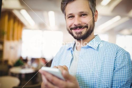 Portrait of businessman using phone in office cafeteria