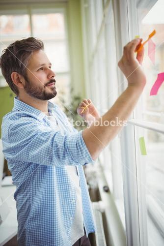 Businessman sticking adhesive notes on window at creative office