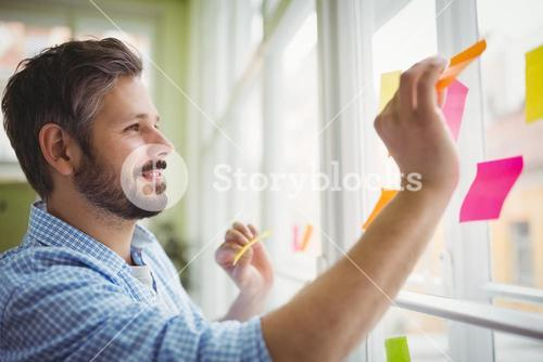 Happy businessman sticking adhesive notes on window at office