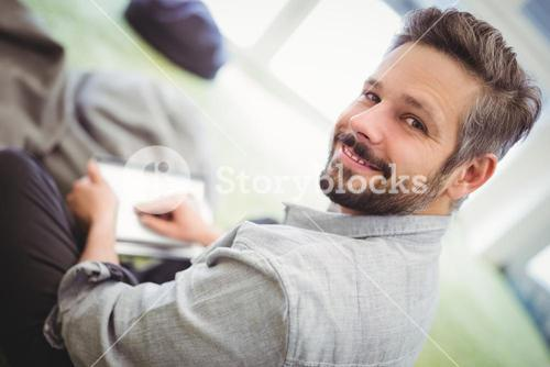 Businessman holding digital tablet in creative office
