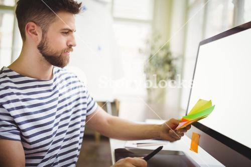 Businessman holding adhesive notes in creative office