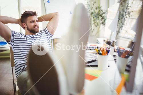 Young businessman relaxing in creative office