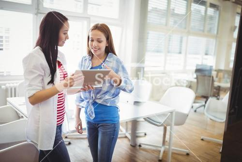Female colleagues discussing with digital tablet in creative office