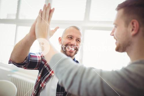 Male coworkers giving high-five