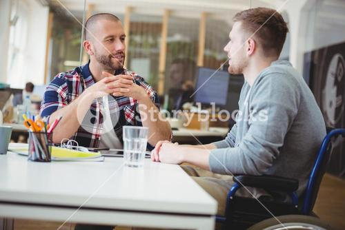 Handicap businessman discussing with colleague in office