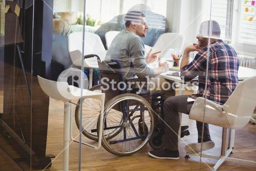 Full length of handicap businessman discussing with colleague
