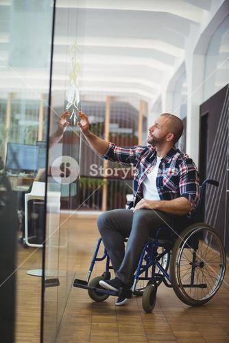 Handicap businessman sticking adhesive notes on glass window