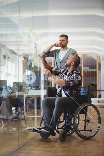Handicap businessman and colleague sticking adhesive notes in office