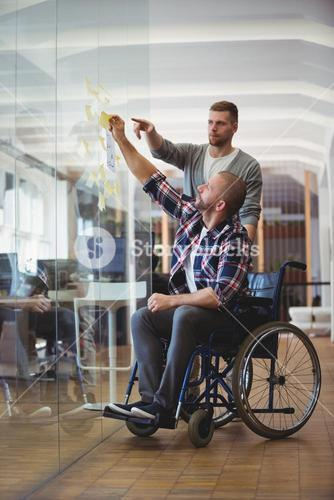 Handicap businessman with colleague sticking adhesive notes in office