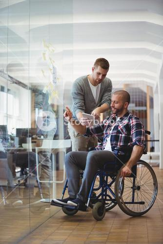 Handicap businessman discussing with colleague at office