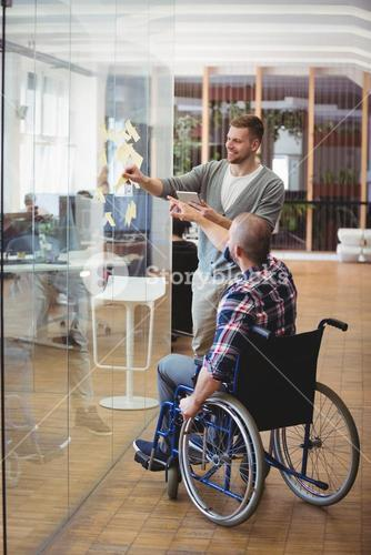 Handicap businessman assisting colleague in creative office