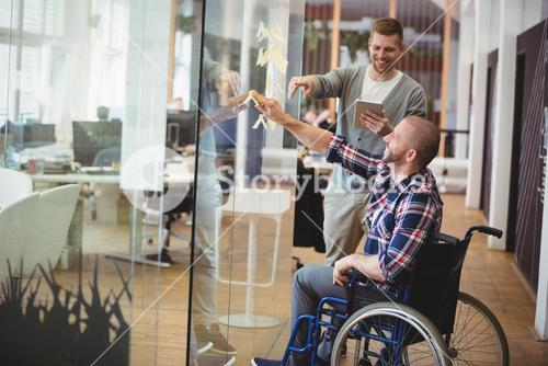 Businessman assisting handicap colleague in creative office