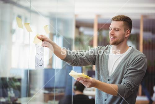 Happy businessman sticking adhesive notes on window in office
