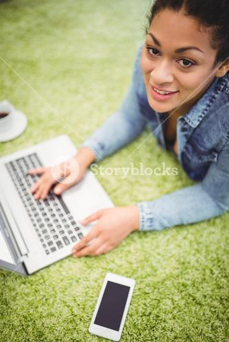 High angle portrait of businesswoman using laptop on carpet