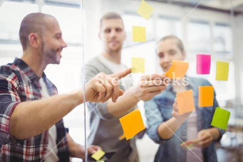 Business people sticking adhesive notes in office