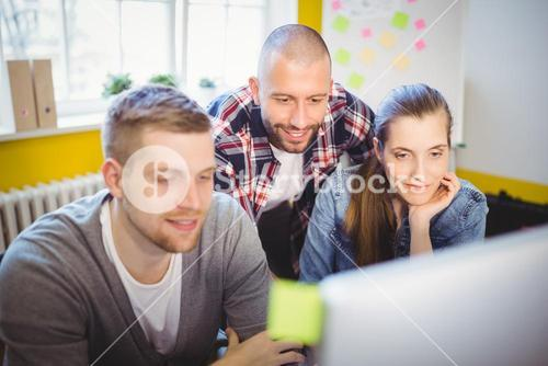 Business people looking at computer in office