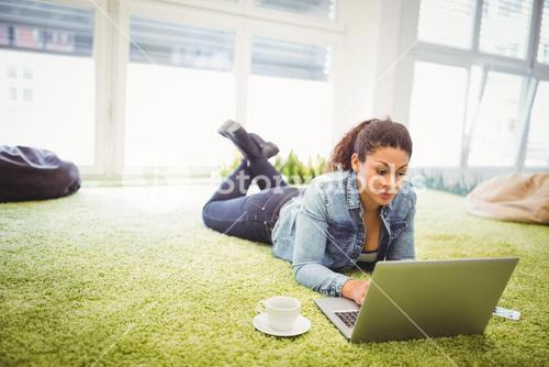 Businesswoman using laptop while lying in creative office