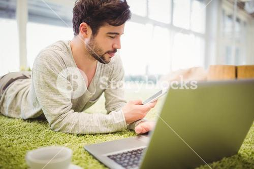 Businessman lying on carpet while using laptop and mobile phone