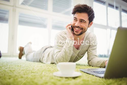 Businessman talking on mobile phone while lying in office