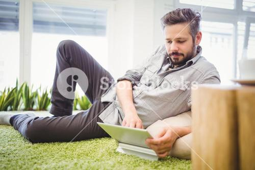 Businessman working on laptop while reclining in office
