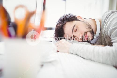 Tired businessman taking nap in office