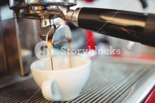 Close-up of espresso maker pouring coffee at cafe
