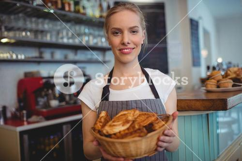 Portrait of confident waitress serving breads at coffee house