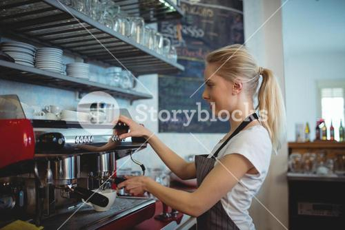 Side view of barista using espresso maker at coffee house