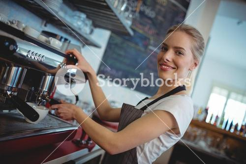 Portrait of happy barista using espresso maker at cafe