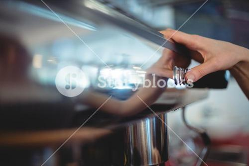 Close-up of barista pushing button on coffee maker at cafeteria