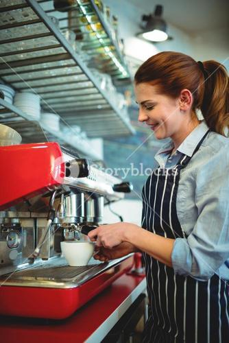 Happy owner using coffee maker at cafe