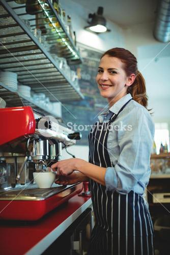 Portrait of waitress pouring coffee from espresso maker